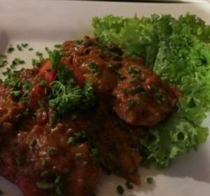 Sausages in dark beer sauce with hot peppers