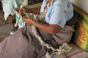 Working the wool into thin strands for weaving.