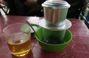 Cambodian filter coffee, served with a glass of jasmine tea, used to dilute the diesel-fuel like consistency of the local coffee.