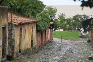 "Colonia's ""Street of Sighs,"" an 18th-century mossy-stoned passageway, lined with ochre and russet stucco buildings."