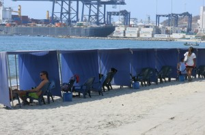 Beach lounging with a calming view of the...shipping yards.